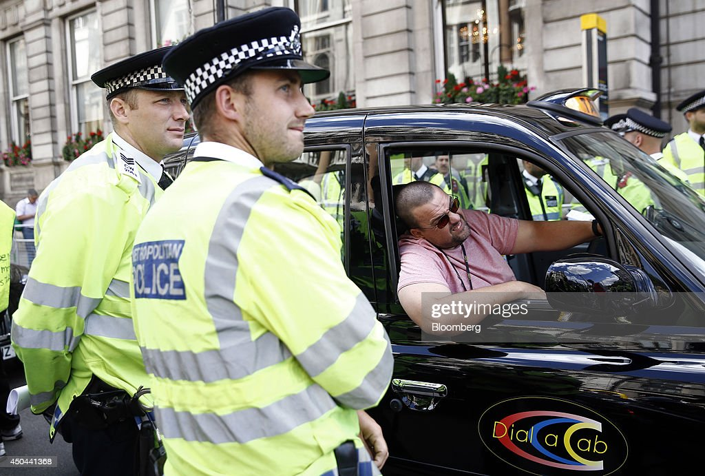 British police officers stand alongside a black London taxi cab parked on Whitehall, during a protest against Uber Technologies Inc.'s car sharing service in London, U.K., on Wednesday, June 11, 2014. Traffic snarled in parts of Madrid and Paris today, with a total of more than 30,000 taxi and limo drivers from London to Berlin blocking tourist centers and shopping districts. Photographer: Simon Dawson/Bloomberg via Getty Images