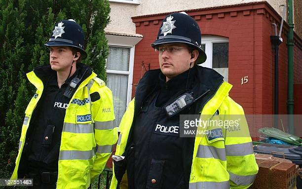 British police officers stand guard outside a house in Luton north of London on December 13 in connection with weekend bombings in Sweden amid...