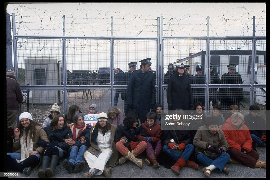 British police officers standing behind protestors participating in anti-nuclear missle demonstration outside Greenham Common Air Base during arrival of US Tomahawk cruise missiles.