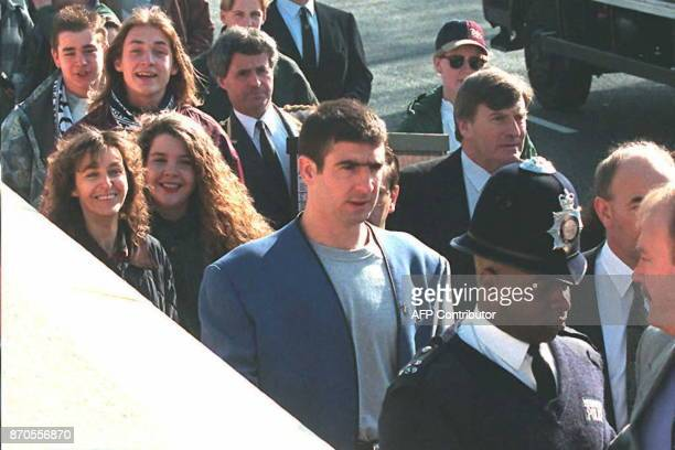 A British policeman escorts soccer star for Manchester United French Eric Cantona as he arrives at East Croydon magistrates court in South London 23...