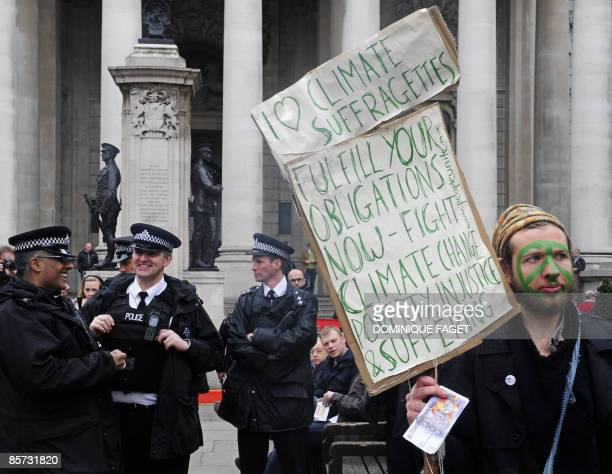 British policemen share a joke as a man protests against Climate Change Poverty and Injustice and Suffering outide the Royal Exchange in London on...