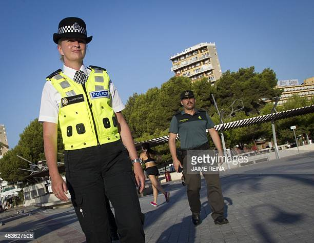 A British policewoman popularly known as 'bobby' walks with a Spanish Civil Guard as they patrol at Punta Ballena street in the holiday resort of...