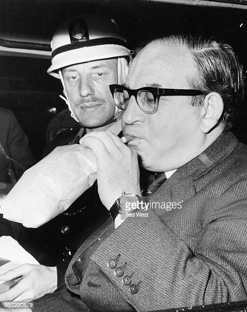 British politician Fred Mulley blowing into a breathalyser with police officer Sergeant Syd Furnell to test the new method London November 11th 1969