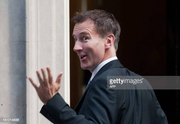 British politician Jeremy Hunt gestures towards the media as he arrives at no 10 Downing Street in central London on September 4 2012 to meet with...