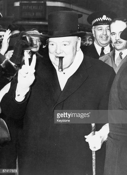 British politician Winston Churchill smoking a cigar and making his famous V sign gesture during an election visit to Glasgow 18th October 1951