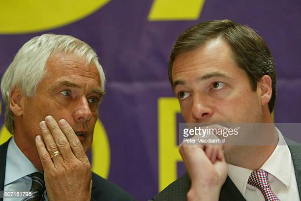 British politicians Robert KilroySilk and Nigel Farage confer during a press conference England May 12 2004 The banner behind them reads 'Say No to...