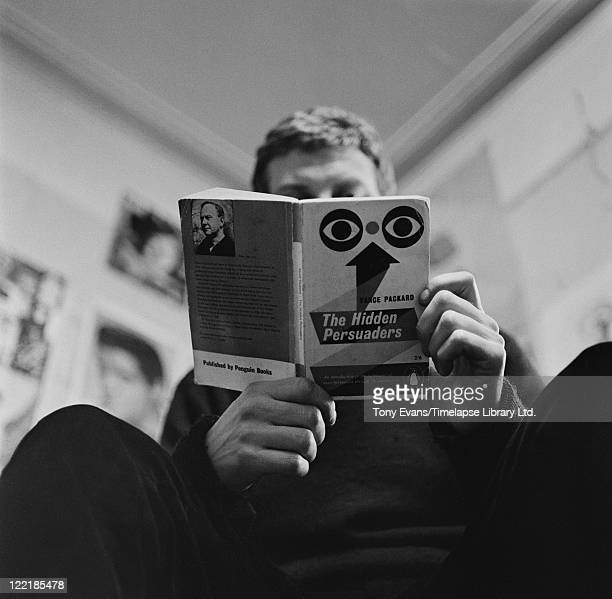 British pop artist artist Derek Boshier reading a copy of Vance Packard's 'The Hidden Persuaders' circa 1965 The book is an examination of...