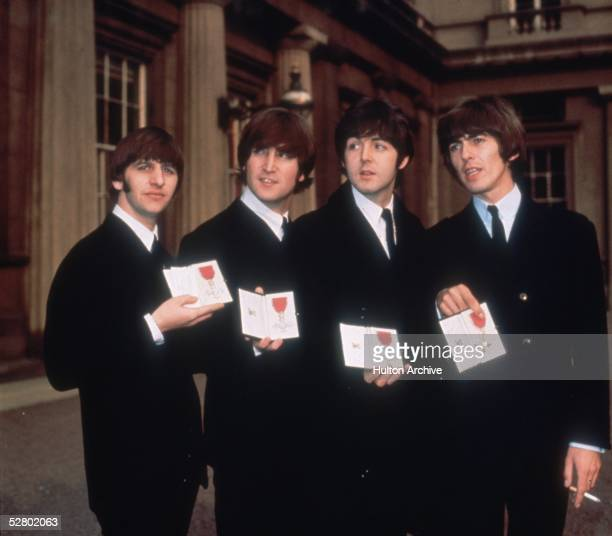 British pop group The Beatles from left to right Ringo Starr John Lennon Paul McCartney and George Harrison outside Buckingham Palace London after...