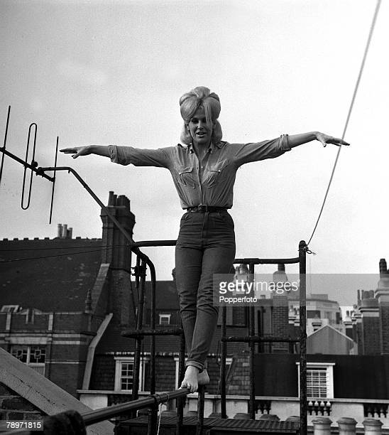British Pop singer Dusty Springfield walking along a metal pole with her arms outsretched to keep her balance on the rooftops 1963