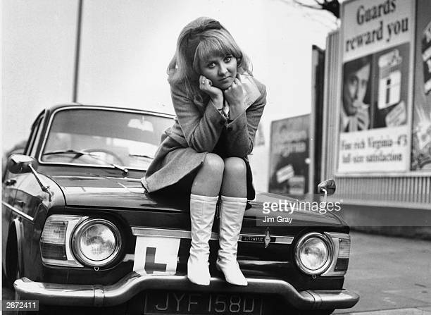 British pop singer Lulu sits on the bonnet of her car looking disappointed after failing her driving test at Isleworth