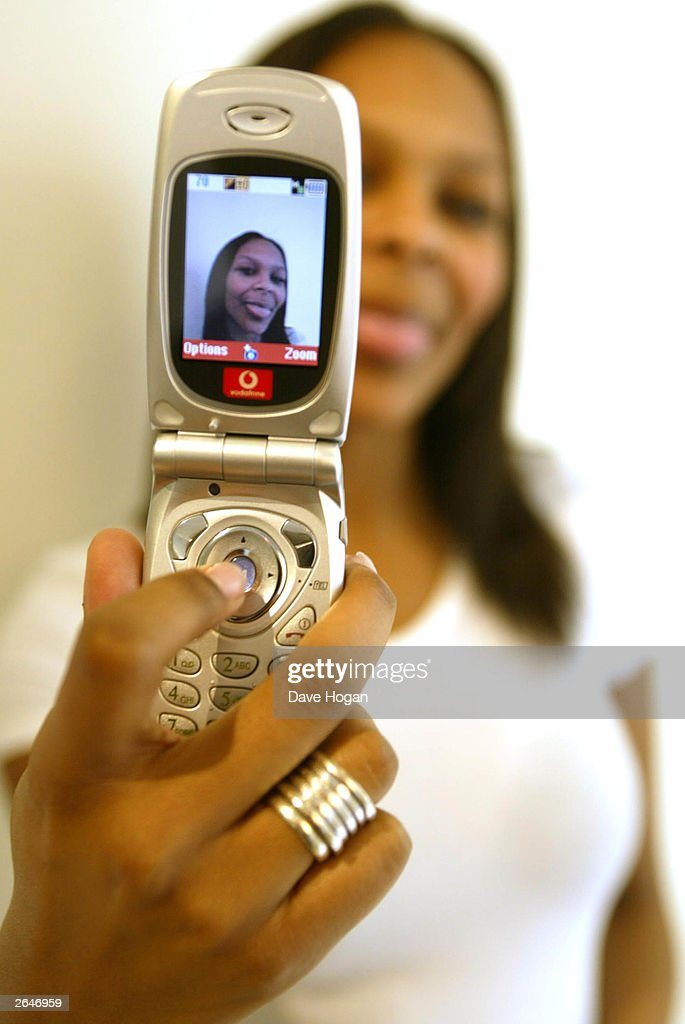 British pop star Samantha Mumba plays with the new Vodafone digital camera mobile phone during a promotional photoshoot on October 26, 2002 in London.