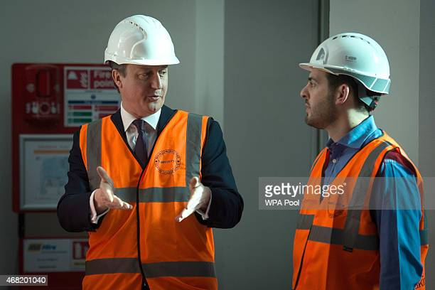 British Prime Minister and leader of the Conservative Party David Cameron talks with a member of staff as he tours an area of the Sainsbury's...