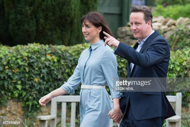British Prime Minister and leader of the Conservative party David Cameron arrives with his wife Samantha to vote at a polling station in Spelsbury on...