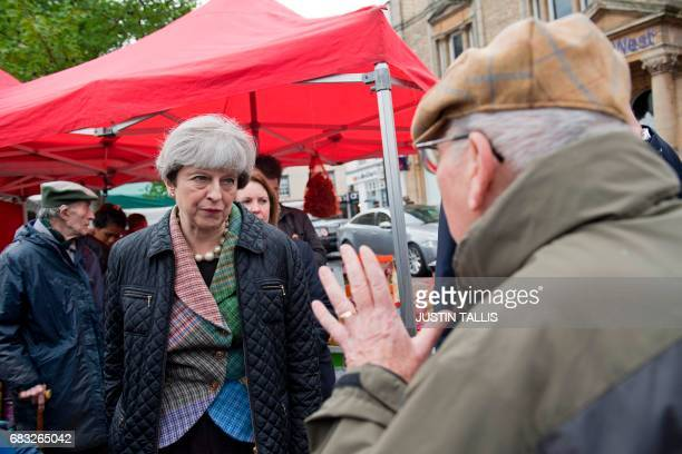 British Prime Minister and leader of the Conservative party Theresa May speaks to a man during an election campaign walk about around Abingdon Market...