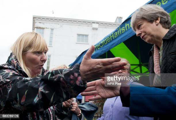 British Prime Minister and leader of the Conservative party Theresa May is confronted by a woman about cuts to her disability benefits during an...