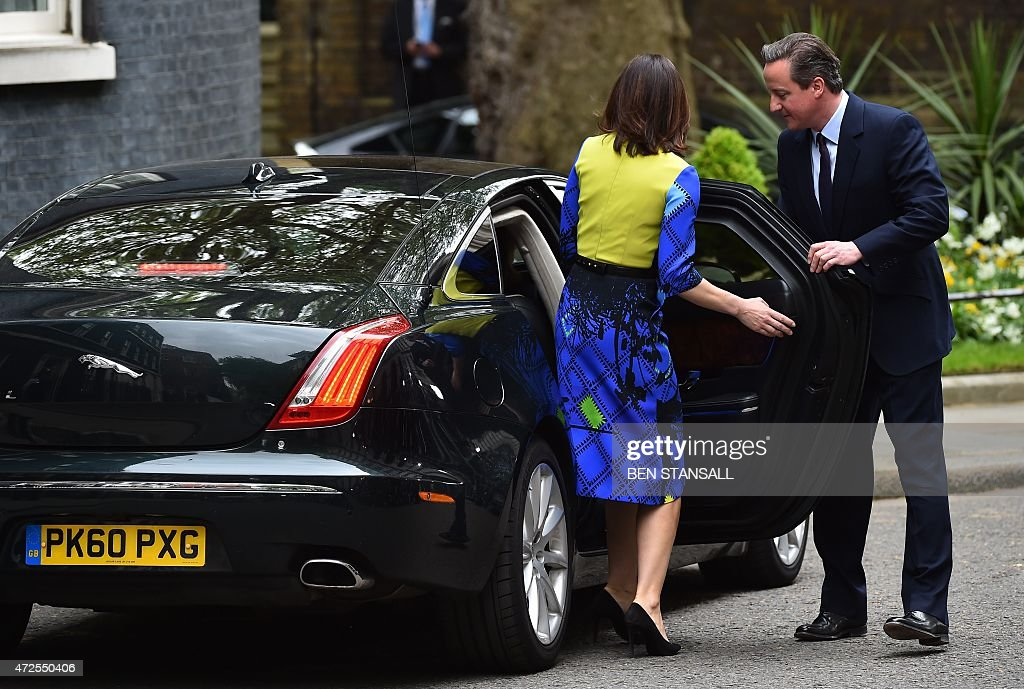 british prime minister and leader of the conservatives david cameron r opens a car door for. Black Bedroom Furniture Sets. Home Design Ideas