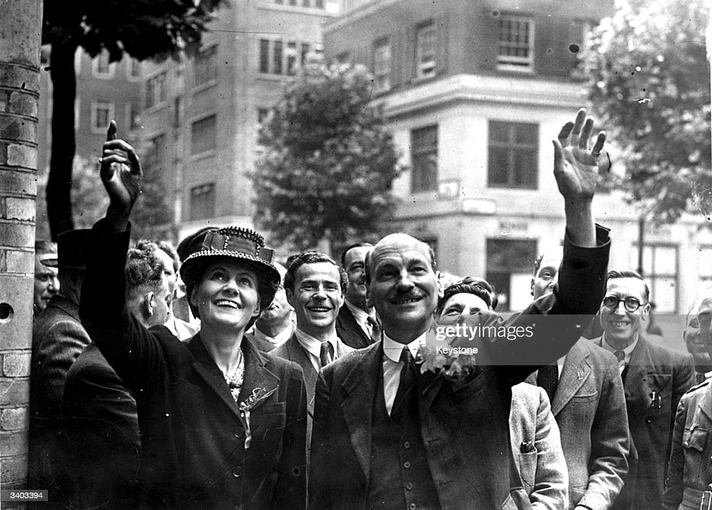 British Prime Minister Clement Attlee (1883 - 1967) and his wife Violet waving to crowds on their arrival at Transport House, London, July 26, 1945.