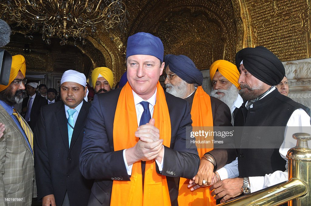 British Prime Minister <a gi-track='captionPersonalityLinkClicked' href=/galleries/search?phrase=David+Cameron+-+Politician&family=editorial&specificpeople=227076 ng-click='$event.stopPropagation()'>David Cameron</a> admiring the beauty of Sanctum Sanctorum of Golden Temple after receiving the rob of honor by Head Granthi Gaini Mal Singh during his visit of Golden Temple, on February 20, 2013 in Amritsar, India.