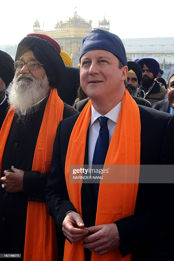 British Prime Minister David Cameron (R) along with Punjab State Chief Minister Parkash Singh Badal (L) visit the Sikh Shrine Golden temple in Amritsar on February 20, 2013. British Prime Minister David Cameron visited the site of a colonial-era massacre in India during his visit to Amritsar, describing the episode as 'deeply shameful' while stopping short of a public apology. On the last leg of a three-day trip aimed at forging deeper economic ties, Cameron took the bold decision to visit the city of Amritsar.