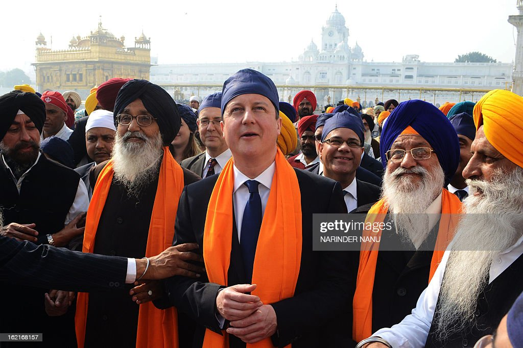 British Prime Minister David Cameron (C) along with Punjab State Chief Minister Parkash Singh Badal (2L), and Shiromani Gurdwara Parbandhak Committee (SGPC) President Avtar Singh Makkar (2R) visit the Sikh Shrine Golden temple in Amritsar on February 20, 2013. British Prime Minister David Cameron visited the site of a colonial-era massacre in India during his visit to Amritsar, describing the episode as 'deeply shameful' while stopping short of a public aAvtar Singh Makkarpology. On the last leg of a three-day trip aimed at forging deeper economic ties, Cameron took the bold decision to visit the city of Amritsar.