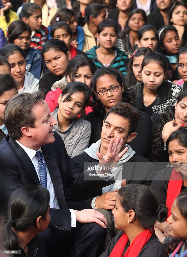 British Prime Minister David Cameron and Bollywood Actor and brand Ambassador of UNICEF Aamir Khan promote child nutrition in India during their interaction with students at Janki Devi Memorial College, on February 19, 2013 in New Delhi, India.