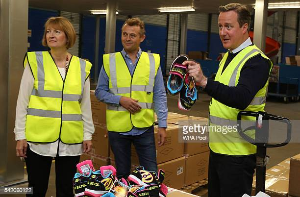 British Prime Minister David Cameron and British Home Secretary Harriet Harman tour sports equipment distributor Shiner Ltd's offices on June 22 2016...