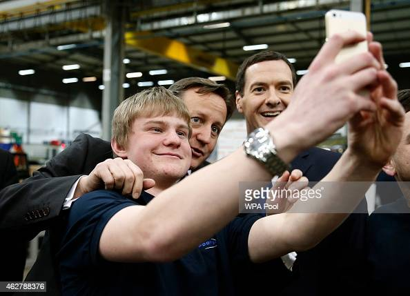 British Prime Minister David Cameron and Chancellor of the Exchequer George Osborne pose for a selfie photograph with an apprentice during a visit to...