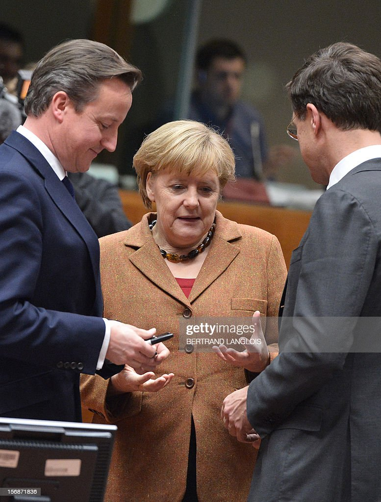 British Prime Minister David Cameron (L) and Dutch Prime Minister Mark Rutte (R) chat with German Chancellor Angela Merkel at the EU Headquarters on November 22, 2012 in Brussels, during a two-day European Union leaders summit called to agree a hotly-contested trillion-euro budget through 2020. European Union officials were scrambling to find an all but impossible compromise on the 2014-2020 budget that could successfully move richer nations looking for cutbacks closer to poorer ones who look to Brussels to prop up hard-hit industries and regions.