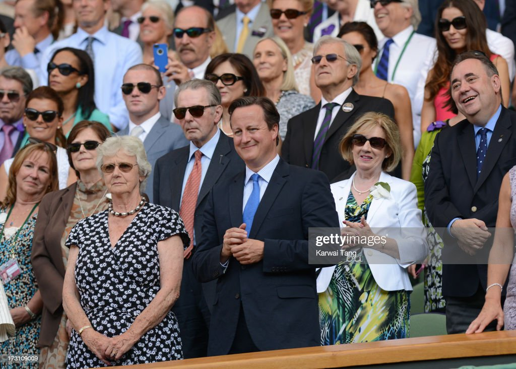 British Prime Minister <a gi-track='captionPersonalityLinkClicked' href=/galleries/search?phrase=David+Cameron+-+Politician&family=editorial&specificpeople=227076 ng-click='$event.stopPropagation()'>David Cameron</a> (C) and First Minister of Scotland <a gi-track='captionPersonalityLinkClicked' href=/galleries/search?phrase=Alex+Salmond&family=editorial&specificpeople=857688 ng-click='$event.stopPropagation()'>Alex Salmond</a> (R) attend the Men's Singles Final between Novak Djokovic and Andy Murray on Day 13 of the Wimbledon Lawn Tennis Championships at the All England Lawn Tennis and Croquet Club on July 7, 2013 in London, England.