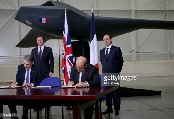 British Prime Minister David Cameron and French President Francois Hollande stand under a concept unmanned Future Combat Air System as they wait for...
