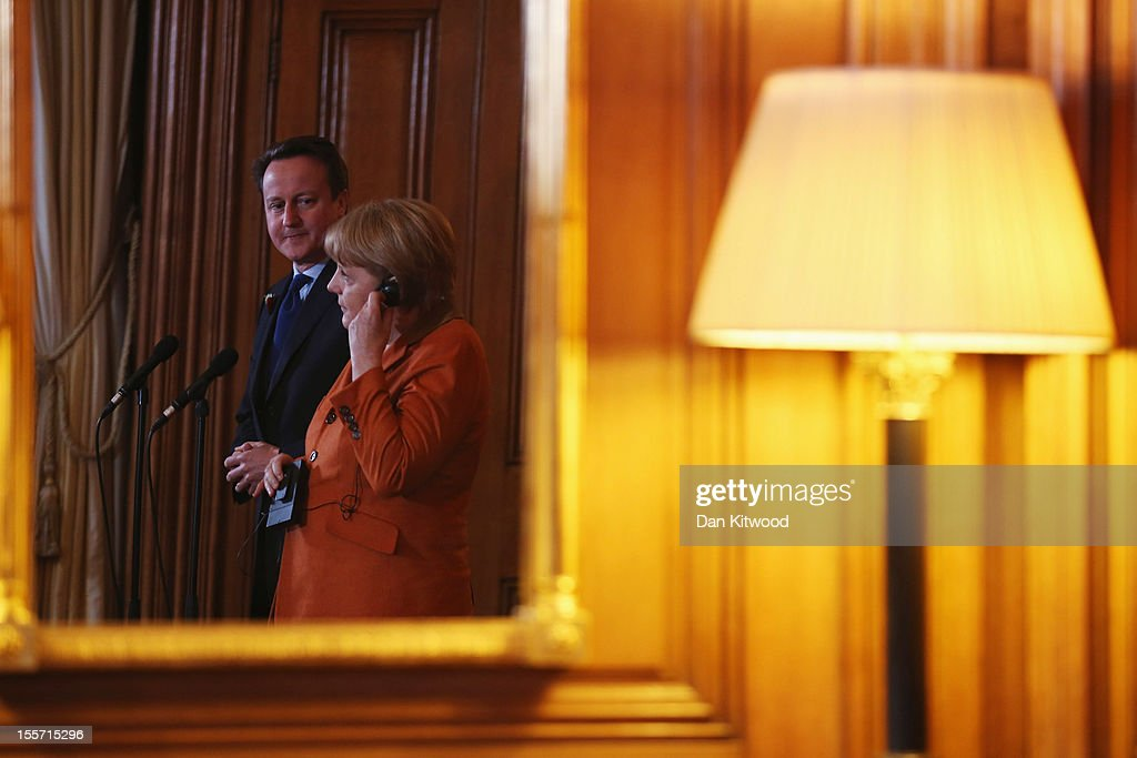 British Prime Minister <a gi-track='captionPersonalityLinkClicked' href=/galleries/search?phrase=David+Cameron+-+Politician&family=editorial&specificpeople=227076 ng-click='$event.stopPropagation()'>David Cameron</a> and German Chancellor <a gi-track='captionPersonalityLinkClicked' href=/galleries/search?phrase=Angela+Merkel&family=editorial&specificpeople=202161 ng-click='$event.stopPropagation()'>Angela Merkel</a> are reflected in a mirror as they speak to the press ahead of a bilateral meeting at 10 Downing Street on November 7, 2012 in London, England. Prime Minister Cameron and Chancellor Merkel are holding talks over increasing the EU's seven year budget, with the Prime Minister urging the Chancellor to stick to an agreement made in 2010 to freeze or cut it.