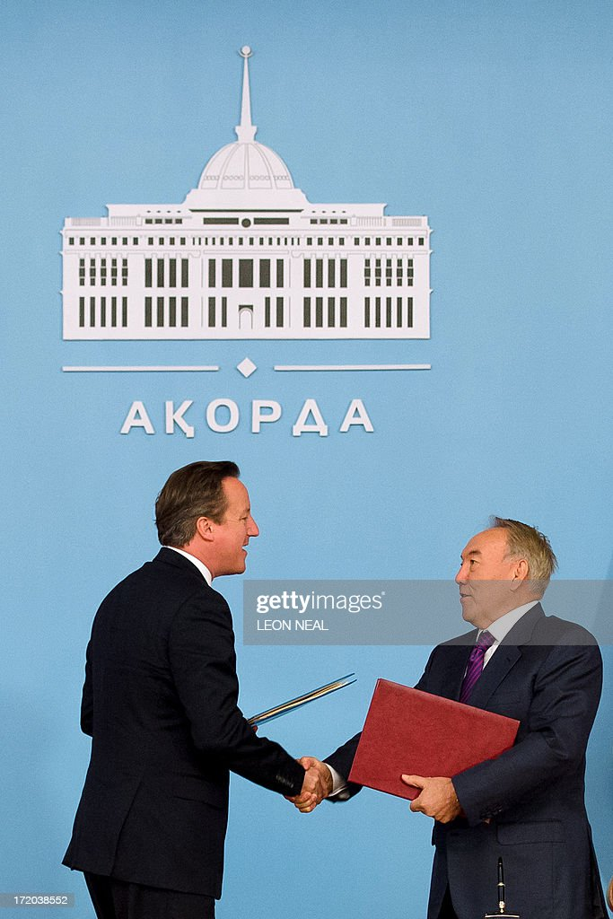 British Prime Minister David Cameron (L) and Kazakhstan President Nursultan Nazarbayev (R) shake hands after signing a strategic partnership agreement at the Presidential Palace in Astana, Kazakhstan on July 1, 2013. David Cameron arrived in Kazakhstan on June 30, 2013 on the first ever trip by a serving British prime minister, hoping to boost trade ties but also promising to raise human rights concerns. AFP PHOTO/POOL/ LEON NEAL