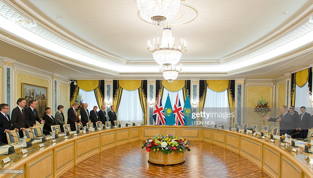 British Prime Minister David Cameron (L) and Kazakhstan President Nursultan Nazarbayev (R) prepare to take their seats ahead of a business-based meeting at the Presidential Palace in Astana, Kazakhstan on July 1, 2013. David Cameron arrived in Kazakhstan on June 30, 2013 on the first ever trip by a serving British prime minister, hoping to boost trade ties but also promising to raise human rights concerns.