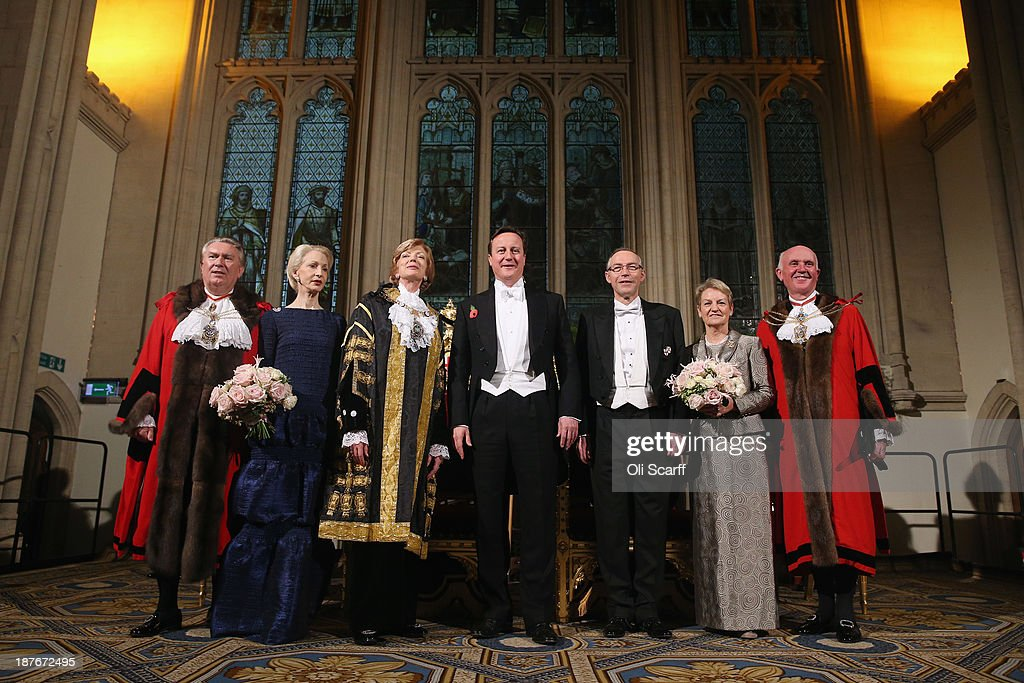 British Prime Minister <a gi-track='captionPersonalityLinkClicked' href=/galleries/search?phrase=David+Cameron+-+Politician&family=editorial&specificpeople=227076 ng-click='$event.stopPropagation()'>David Cameron</a> (C) arrives in the Guildhall to attend The Lord Mayor's Banquet on November 11, 2013 in London, England. The New Lord Mayor of London Fiona Woolf is hosting the annual Lord Mayor's Banquet in London's Guildhall which will feature speeches from the Prime Minister and the Archbishop of Canterbury. Alderman Fiona Woolf has been elected as 686th Lord Mayor of the City of London and the second ever woman to hold the role. From left to right Sheriff Alderman Sir Paul Judge; Lady Judge; Lord Mayor of London Fiona Woolf; Prime Minister <a gi-track='captionPersonalityLinkClicked' href=/galleries/search?phrase=David+Cameron+-+Politician&family=editorial&specificpeople=227076 ng-click='$event.stopPropagation()'>David Cameron</a>; Nicholas Woolf, the Lord Mayor's husband, Angela Waddingham; Sheriff Adrian Waddingham.