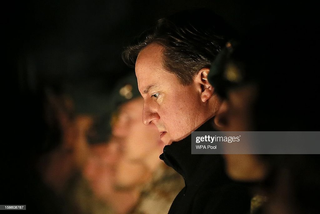 British Prime Minister <a gi-track='captionPersonalityLinkClicked' href=/galleries/search?phrase=David+Cameron+-+Politician&family=editorial&specificpeople=227076 ng-click='$event.stopPropagation()'>David Cameron</a> attends a carol service with British, Danish and Bosnian soldiers on December 20, 2012 in Helmand Province, Afghanistan. Prime Minister Cameron is making a Christmas visit to British troops in the region amid tight security.