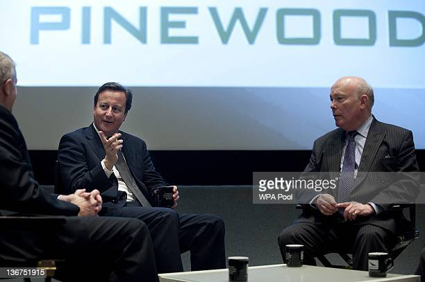 British Prime Minister David Cameron attends a meeting with British writer and actor Julian Fellows and CEO of Pinewood Group Ivan Dunleavy during a...