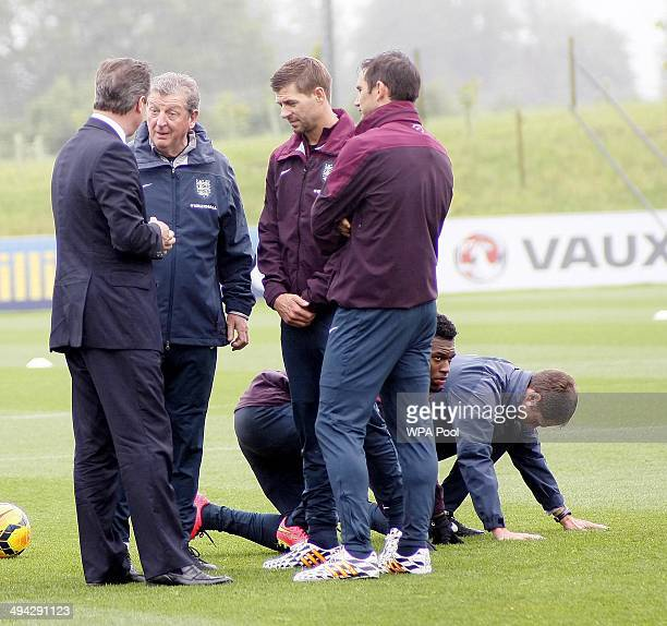 British Prime Minister David Cameron chats with England football manager Roy Hodgson England footballers Frank Lampard and Steven Gerrard as Daniel...