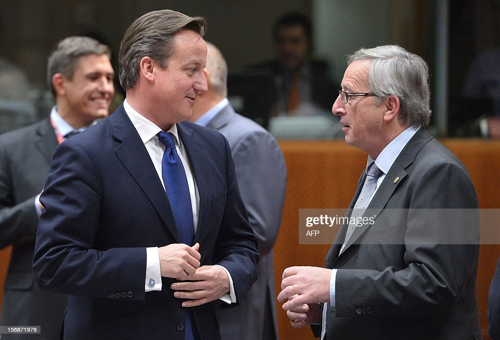 British Prime Minister David Cameron (L) chats with Luxembourg Prime Minister Jean-Claude Juncker at the EU Headquarters on November 22, 2012 in Brussels, during a two-day European Union leaders summit called to agree a hotly-contested trillion-euro budget through 2020. European Union officials were scrambling to find an all but impossible compromise on the 2014-2020 budget that could successfully move richer nations looking for cutbacks closer to poorer ones who look to Brussels to prop up hard-hit industries and regions. AFP PHOTO / BERTRAND LANGLOIS