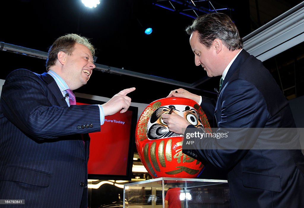 British Prime Minister David Cameron colours in the eye of a Daruma doll, a Japanese tradition symbolising the completion of a goal or project, watched by Nissan Executive Vice President Andy Palmer (L) during a visit to the Nissan factory in Sunderland, northeast England on March 28, 2013. Cameron visited the Sunderland manufacturing plant of Japanese auto-maker Nissan in Sunderland on March 28 as it was announced that the factor will start production of the Leaf electric vehicle. AFP PHOTO / POOL / ANNA GOWTHORPE