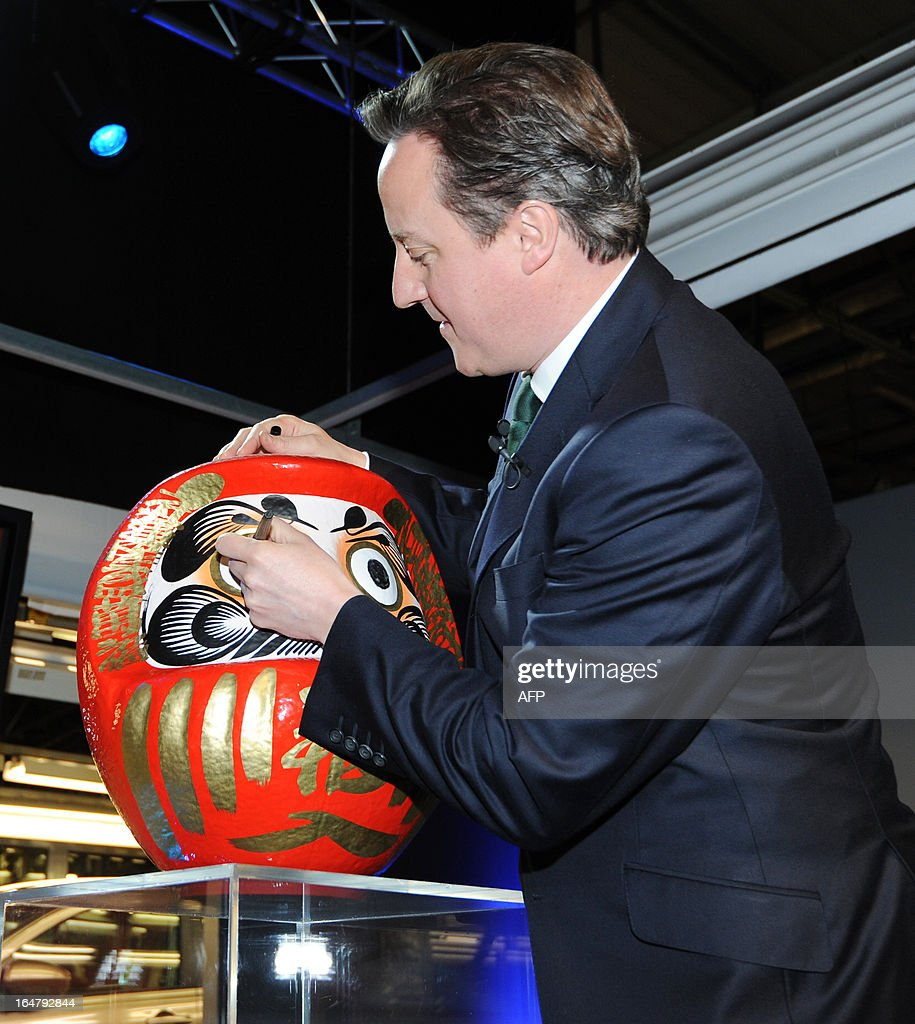 British Prime Minister David Cameron colours in the eye of a Daruma doll, a Japanese tradition symbolising the completion of a goal or project, during a visit to the Nissan factory in Sunderland, northeast England on March 28, 2013. Cameron visited the Sunderland manufacturing plant of Japanese auto-maker Nissan in Sunderland on March 28 as it was announced that the factor will start production of the Leaf electric vehicle. AFP PHOTO / POOL / ANNA GOWTHORPE