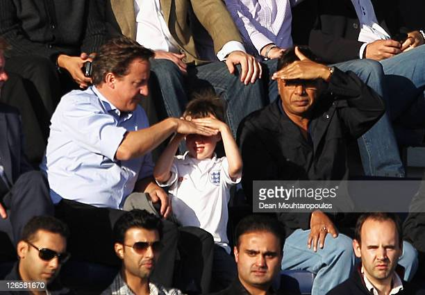 British Prime Minister David Cameron covers his son Arthurs' eyes from the sun as they sit with Indian Steel Magnate Lakshmi Mittal during the...