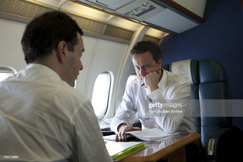 British Prime Minister David Cameron (right) deep in thought over Europe as he listens to Chancellor George Osborne during an RAF flight taking them to attend the G20 Summit in Cannes, France, 3rd November 2011.