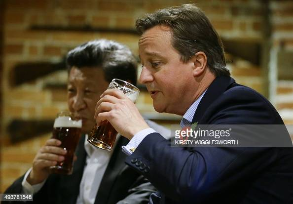 British Prime Minister David Cameron drinks a pint of beer with Chinese President Xi Jinping at a pub in Princess Risborough near Chequers northwest...