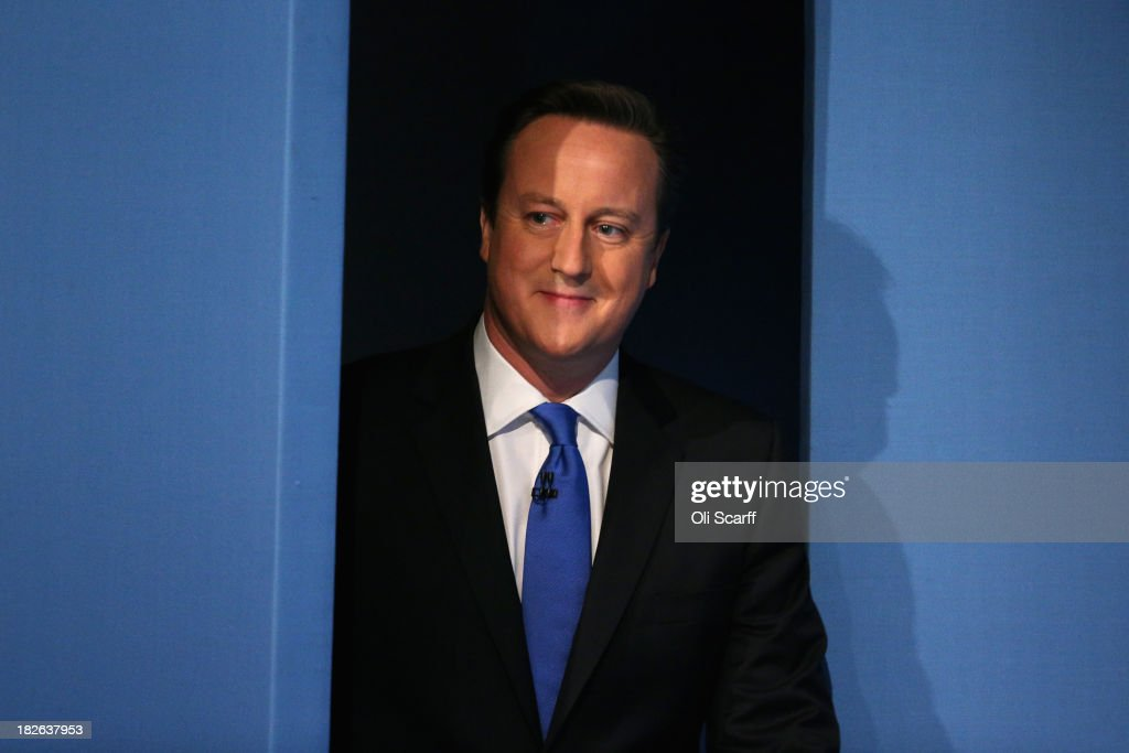 British Prime Minister David Cameron enters the stage to deliver his keynote speech on the last day of the annual Conservative Party Conference at...
