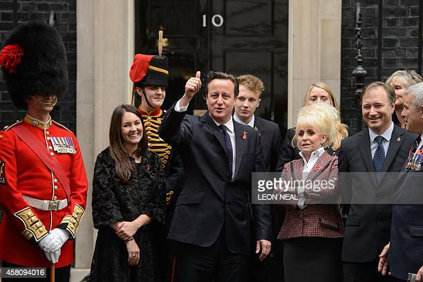 British Prime Minister David Cameron gestures as he joins British celebrities including actresses Barbara Windsor and Lacey Turner and military...