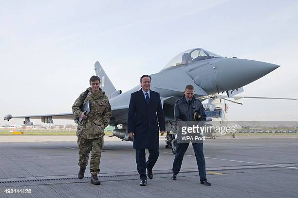 British Prime Minister David Cameron gestures as he walks with Group Captain David Manning past an RAF Eurofighter Typhoon fighter jet and a Royal...