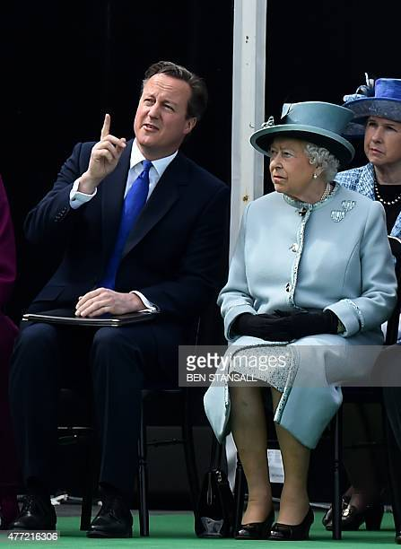 British Prime Minister David Cameron gestures sat next to Britain's Queen Elizabeth II as they attend a service to mark the 800th anniversary of...