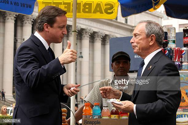 British Prime Minister David Cameron gives a thumbs up after eating a hot dog with New York City Mayor Michael Bloomberg outside Penn Station on July...