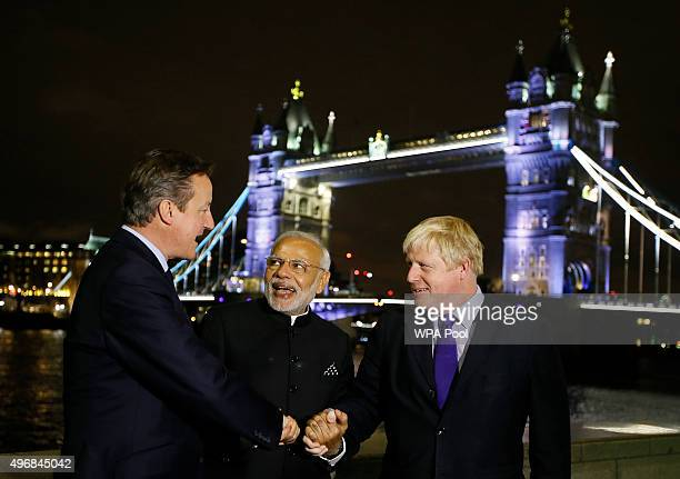 British Prime Minister David Cameron Indian Prime Minister Narendra Modi and Mayor of London Boris Johnson hold hands in front of Tower Bridge during...