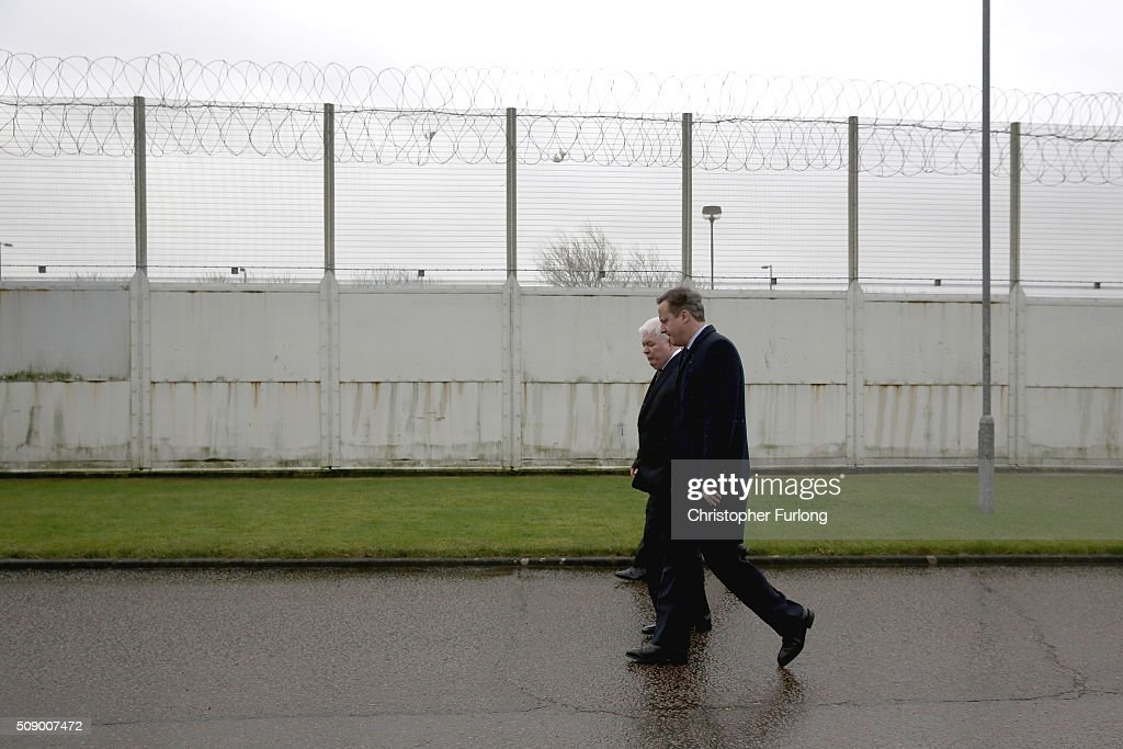 British Prime Minister David Cameron is escorted by prison governor Stephen Ruddy (L) as he tours HMP Onley ahead of a major speech on prison reform today on February 8, 2016 in Rugby, England. David cameron is due to announce six 'reform prisons'will be created in England in Wales as part of the governments prison reform.